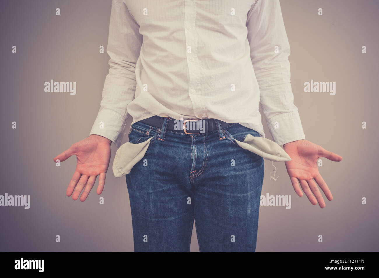 Young broke man is showing his empty pockets - Stock Image