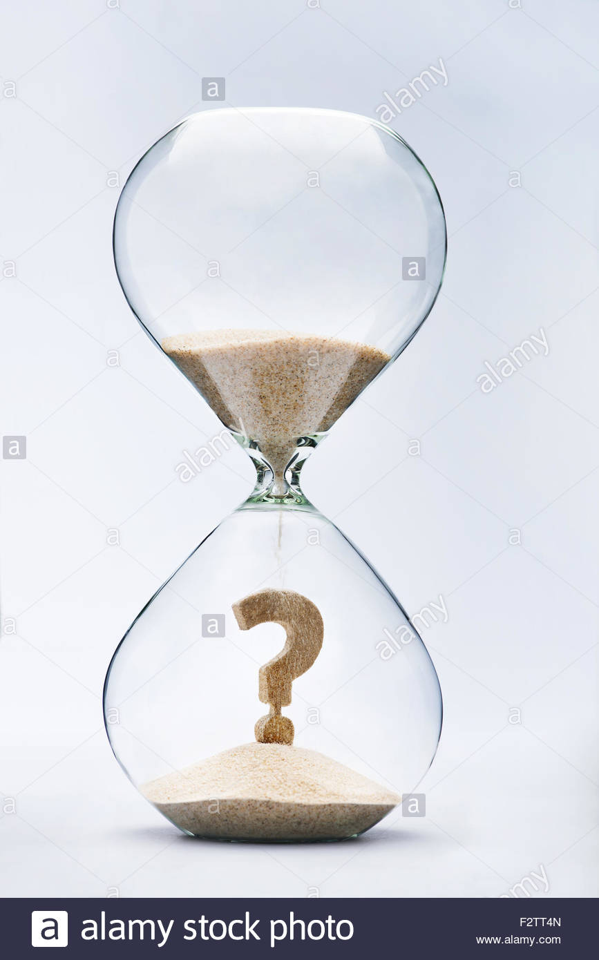 Question Mark made out of falling sand inside hourglass - Stock Image