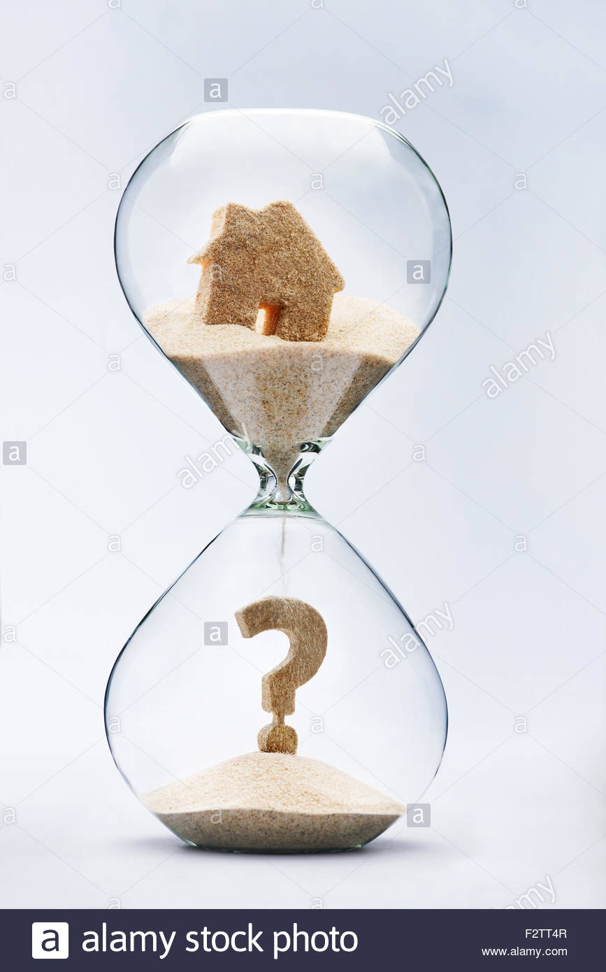 Real estate concept. Question mark made out of falling sand from house flowing through hourglass - Stock Image