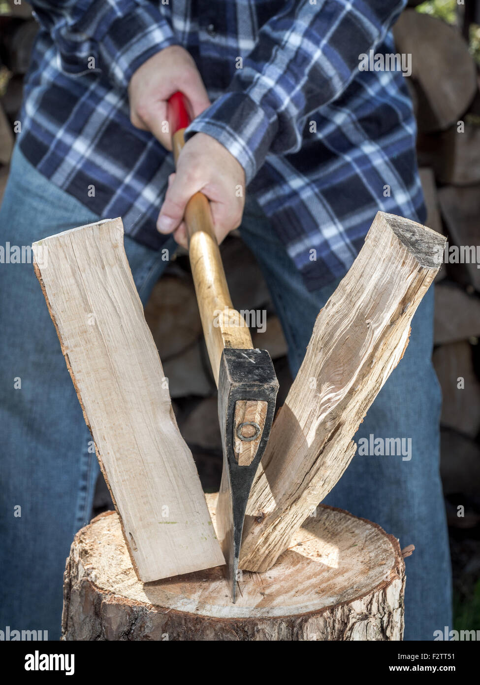 Man splitting log on chopping block with axe - Stock Image