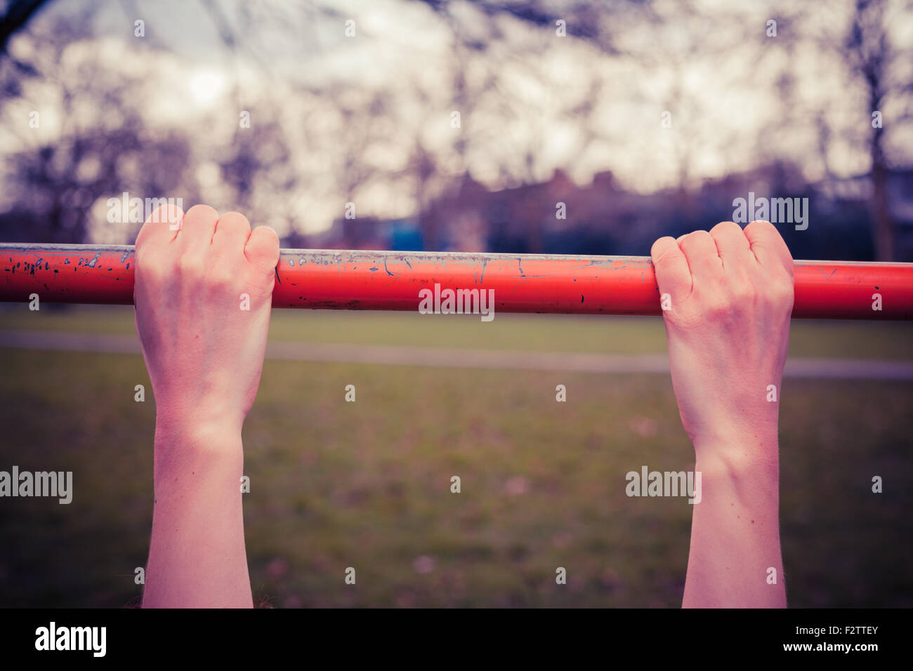Closeup on a young woman's hands as she is hanging from a monkey bar in the park - Stock Image