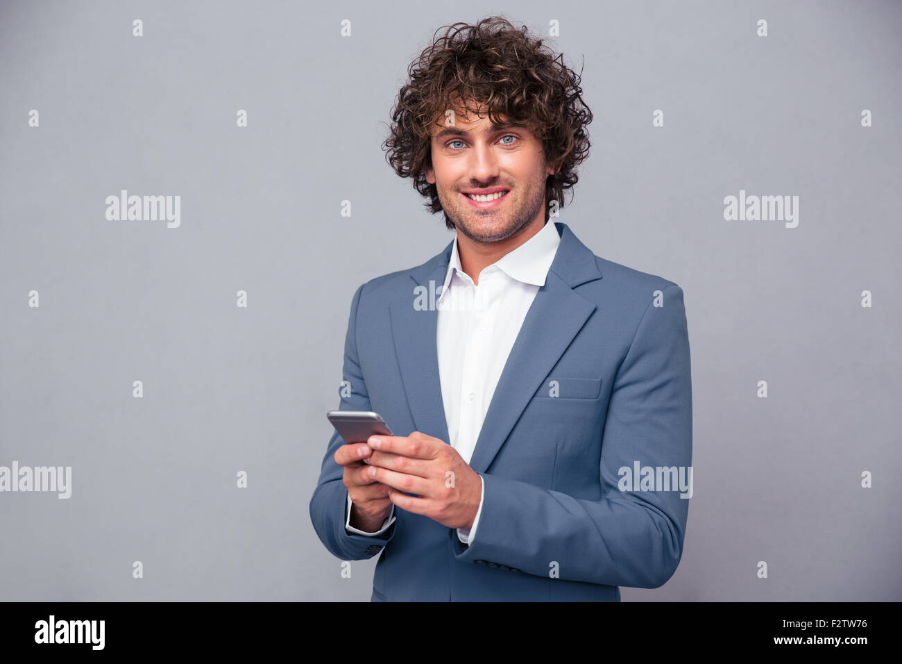 Portrait of a happy businessman holding smartphone and looking at camera over gray background Stock Photo