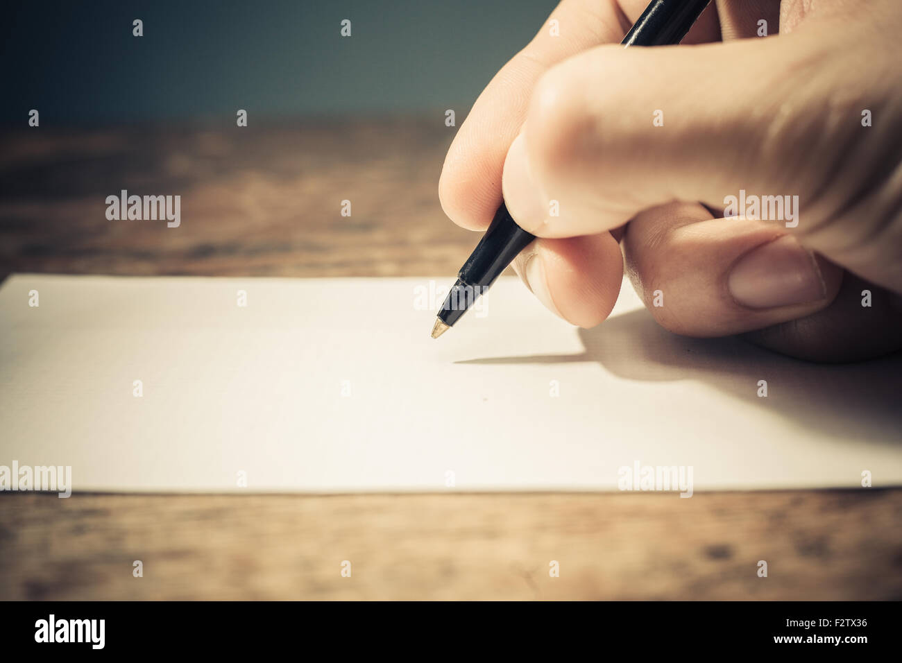 Closeup on a man's hand writing on apiece of paper with a pen - Stock Image