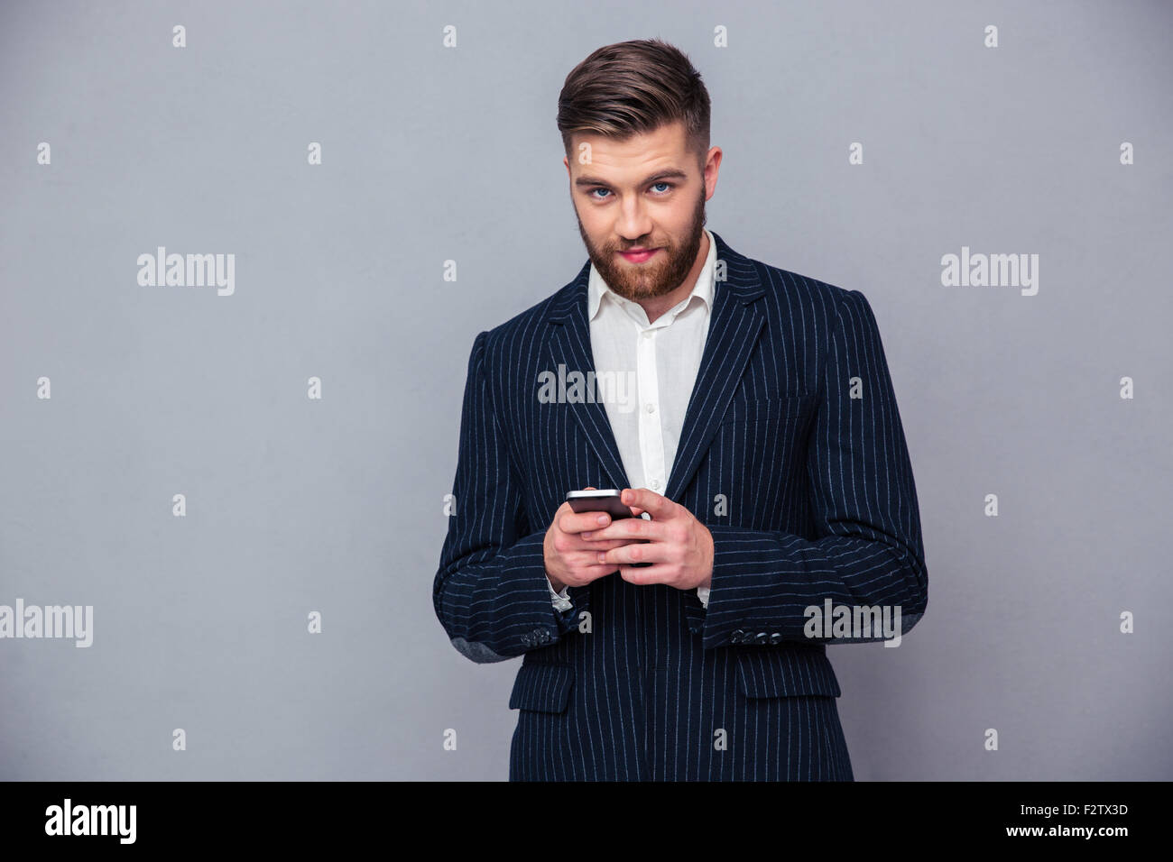 Portrait of a handsome businessman using smartphone over gray background and looking at camera Stock Photo