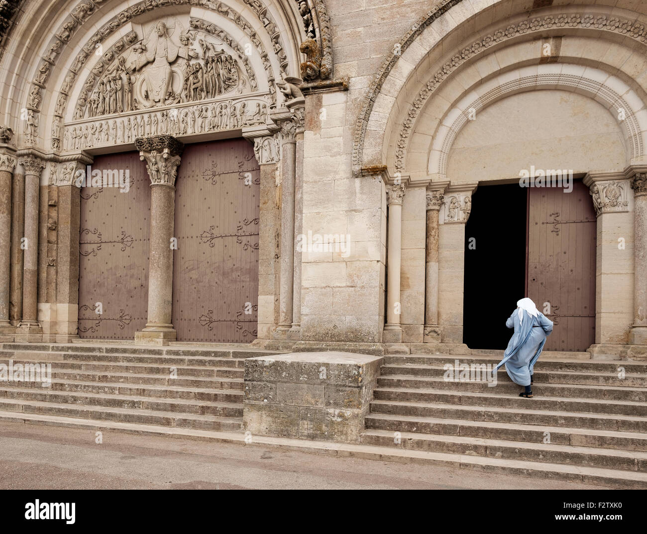 A nun holds her hood in the wind as she hurries across the square in front of the Abbey of Vézelay, the Basilica - Stock Image