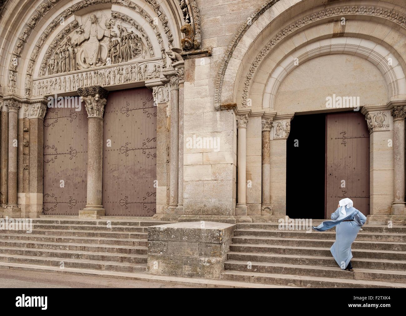 A nun holds her hood in the wind as she hurries up the steps of the Abbey of Vézelay, the Basilica of St Magdelene - Stock Image