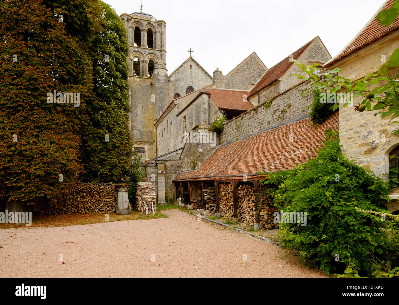 Outbuildings in the Abbey of Vezelay. A belltower of Basilique Sainte-Madeleine is in the background. - Stock Image