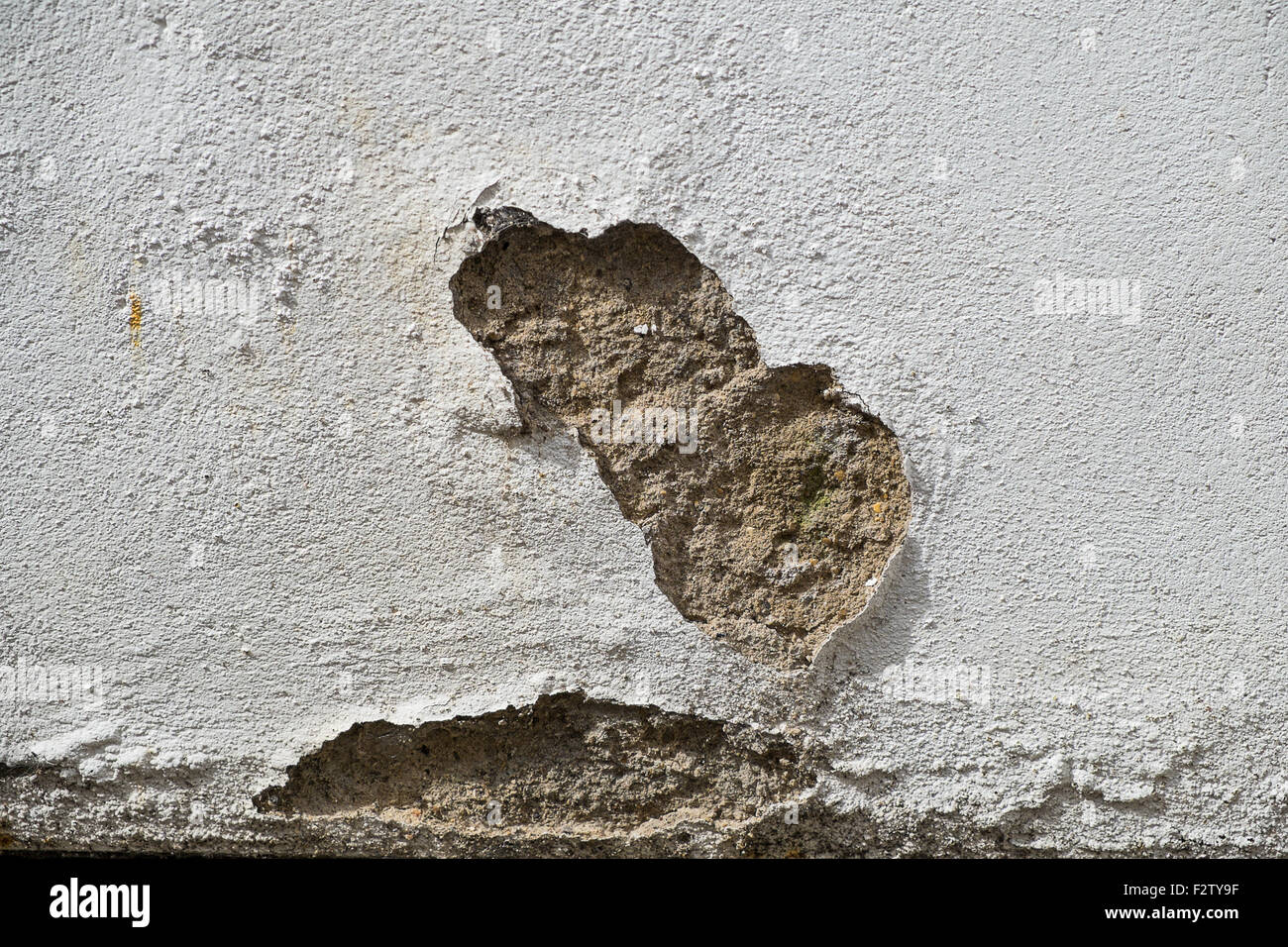 outside wall showing patch of damaged render - Stock Image