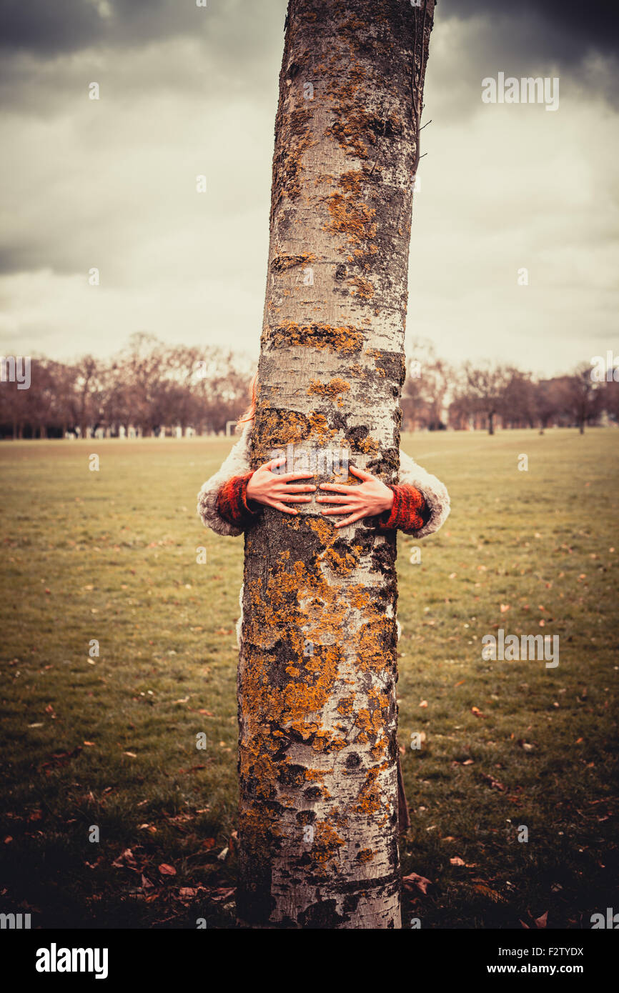 Young woman is in the park on a winter's day and is hugging a tree Stock Photo