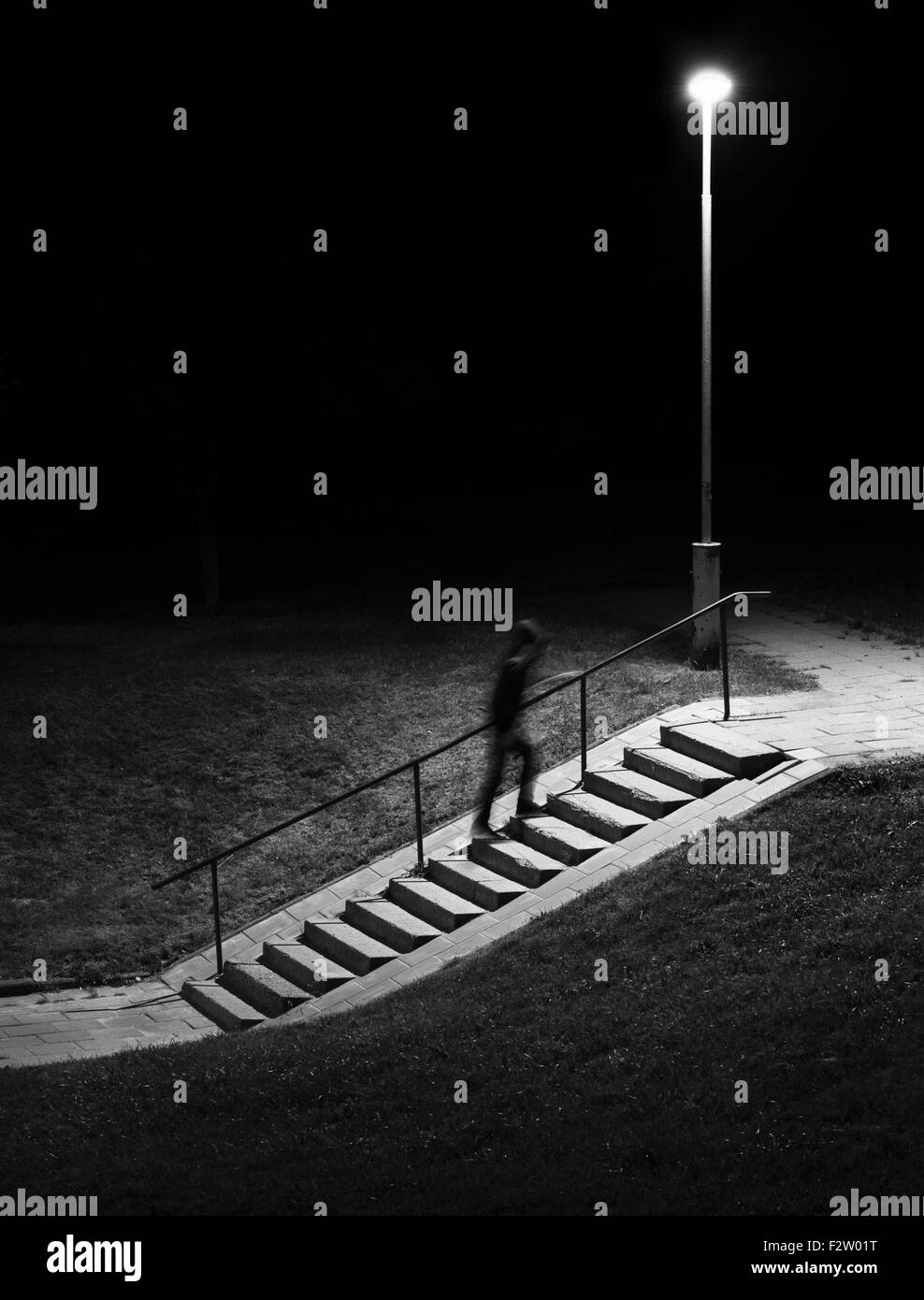 Night scene. Human figure in motion blur walking up stairs. - Stock Image