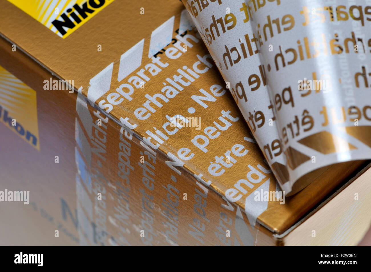 Tamper-proof security tape on the packaging of a new Nikon lens - Stock Image
