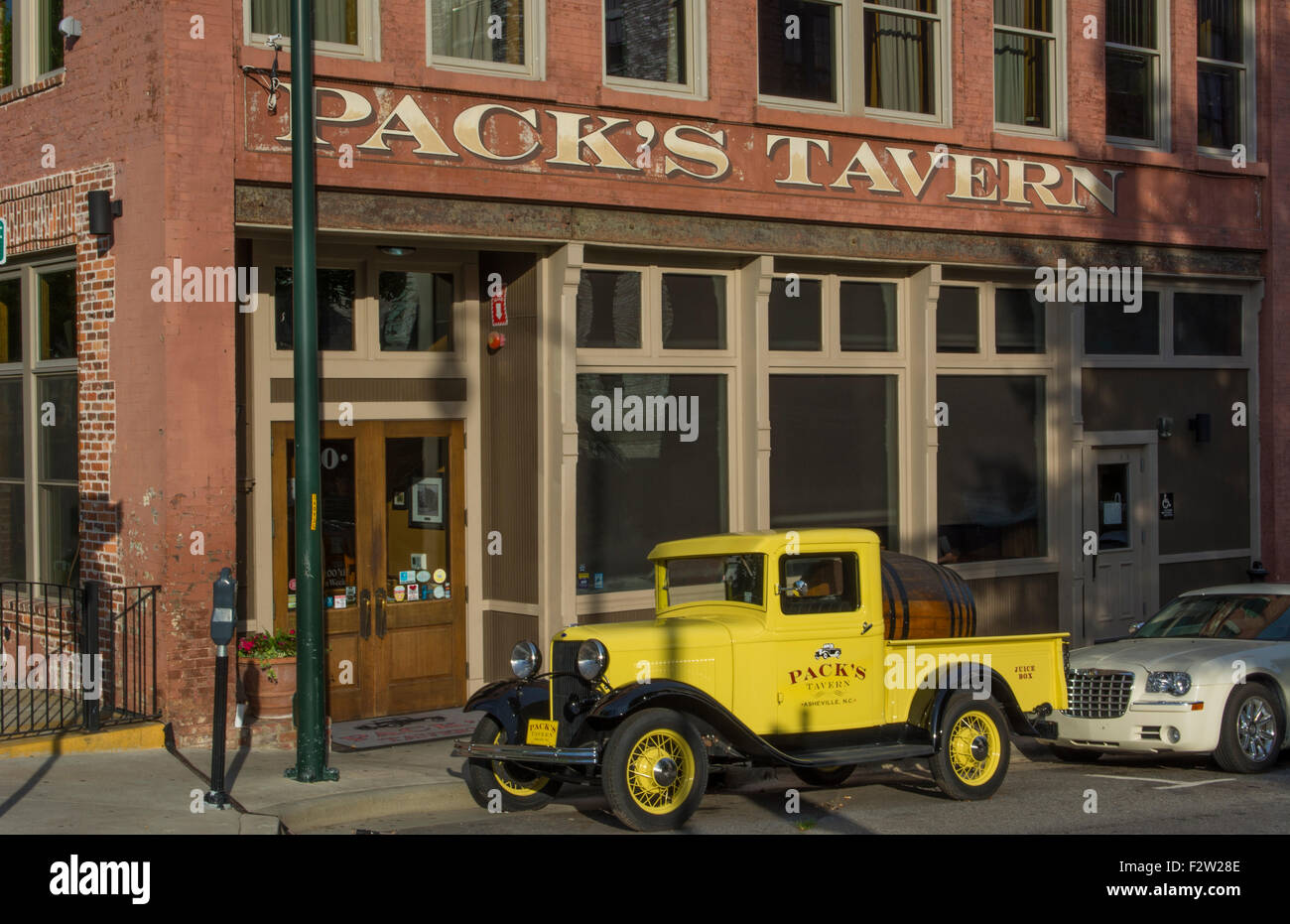 Asheville North Carolina Pack Square with yellow old historic truck at Pack's Tavern in vintage building - Stock Image