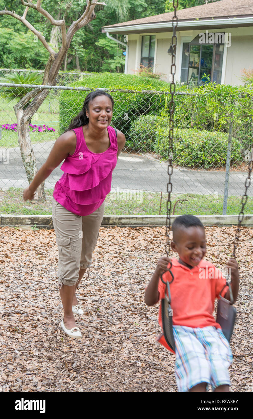 Black single mother swinging her 3 year old son on swings at park having fun together MR-7 MR -10 Model released - Stock Image