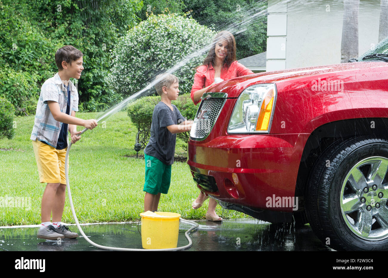 Single mother washing car at home with her two children in driveway with hose MR-11, MR-12, MR-13 Model Released - Stock Image