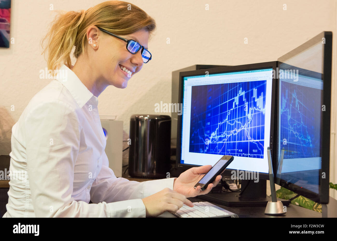 Young woman working at home office using cell phone and two computer monitors doing business with clients on the - Stock Image