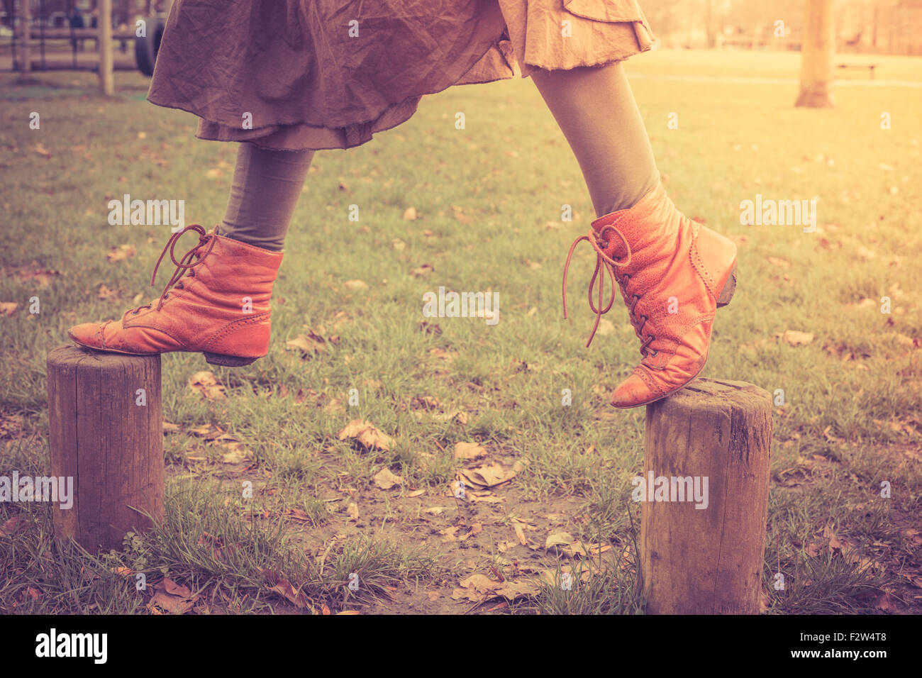 A woman is playfully walking on some small wooden posts in the park - Stock Image