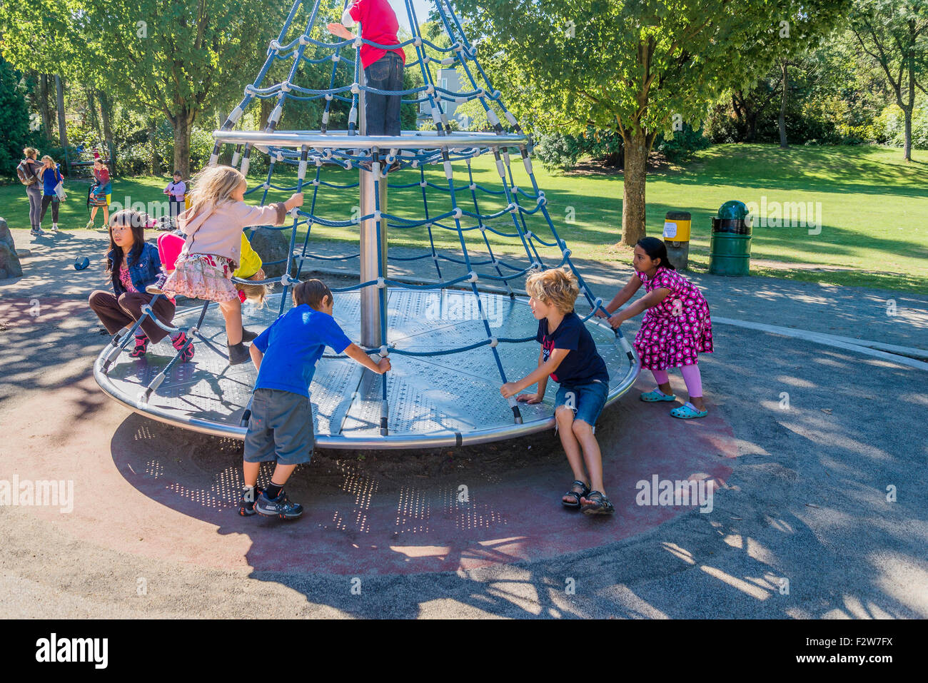 kids playing on roundabout in playground - Stock Image