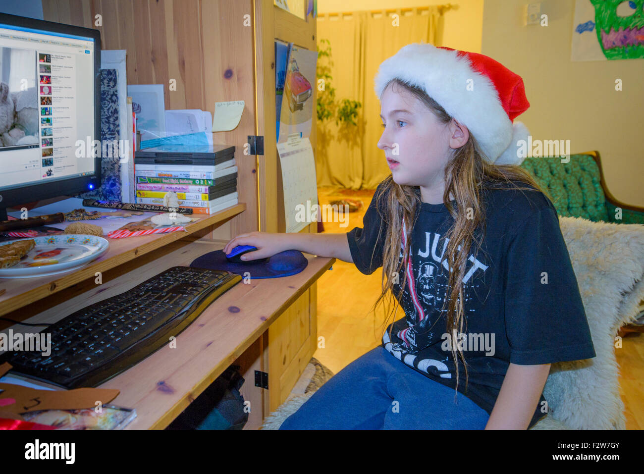 Long haired boy with santa hat using computer. - Stock Image
