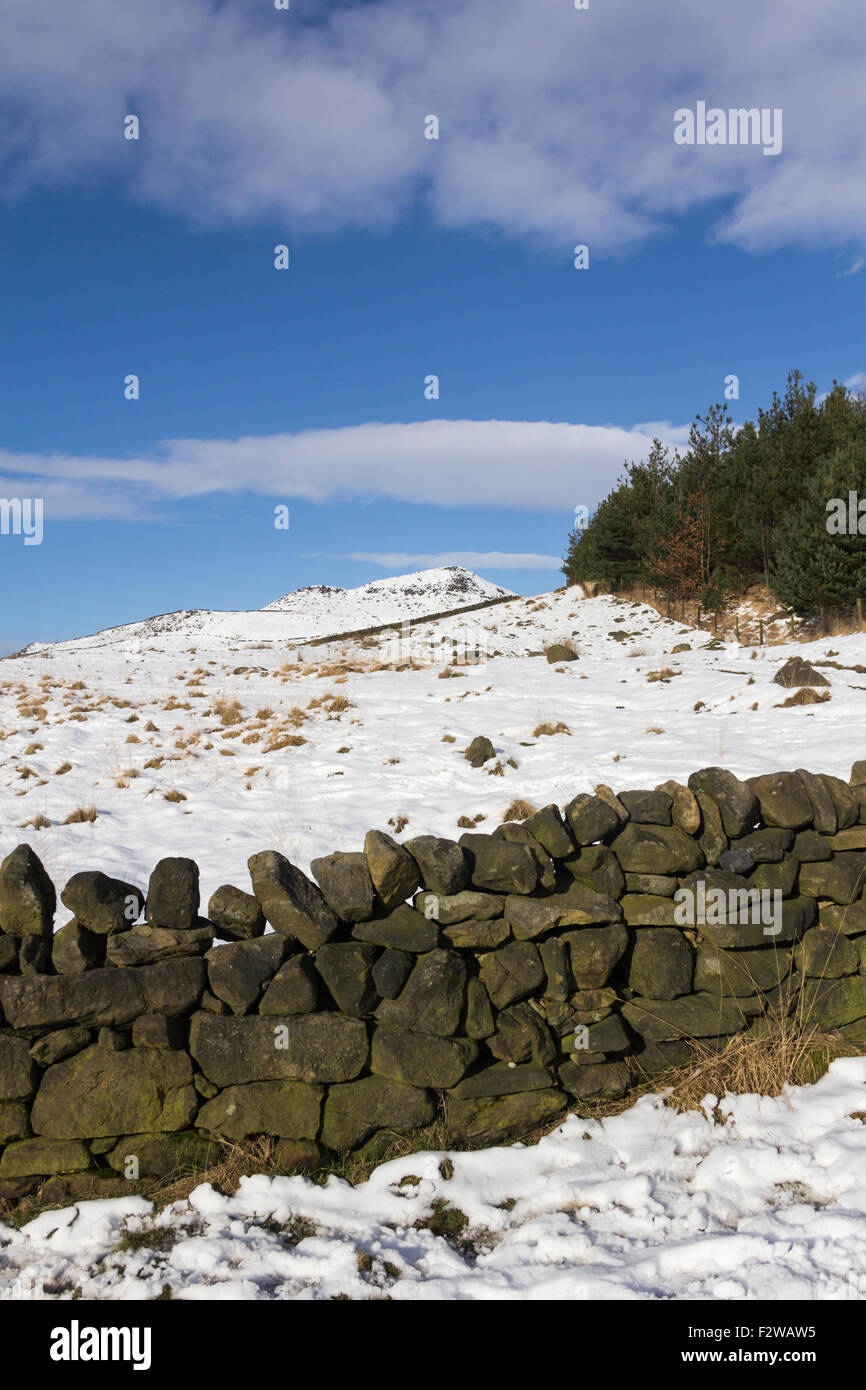 Snow covered hill beyond a dry stone wall near Dovestone reservoir, Saddleworth. Dovestone reservoir lies between - Stock Image