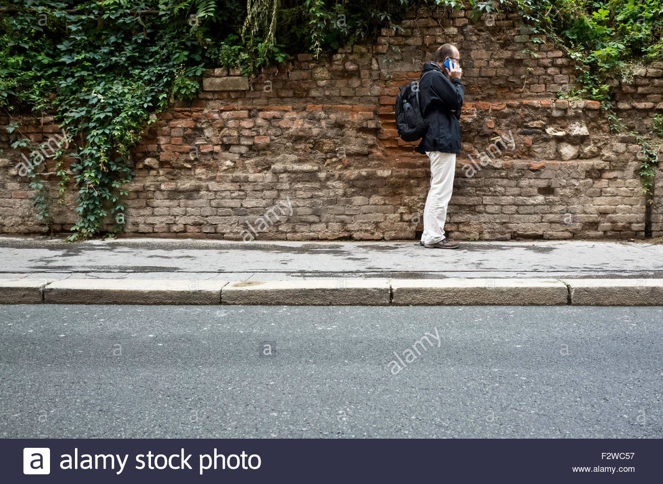 man standing on a sidewalk and calling with a cellphone - Stock Image