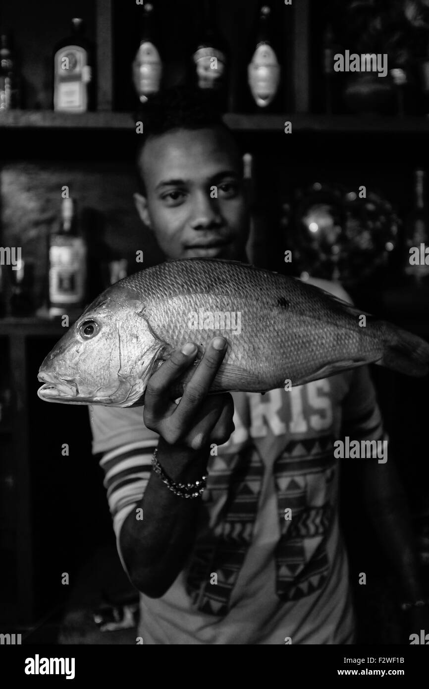 A young Cuban man showing one of his line caught fish. - Stock Image