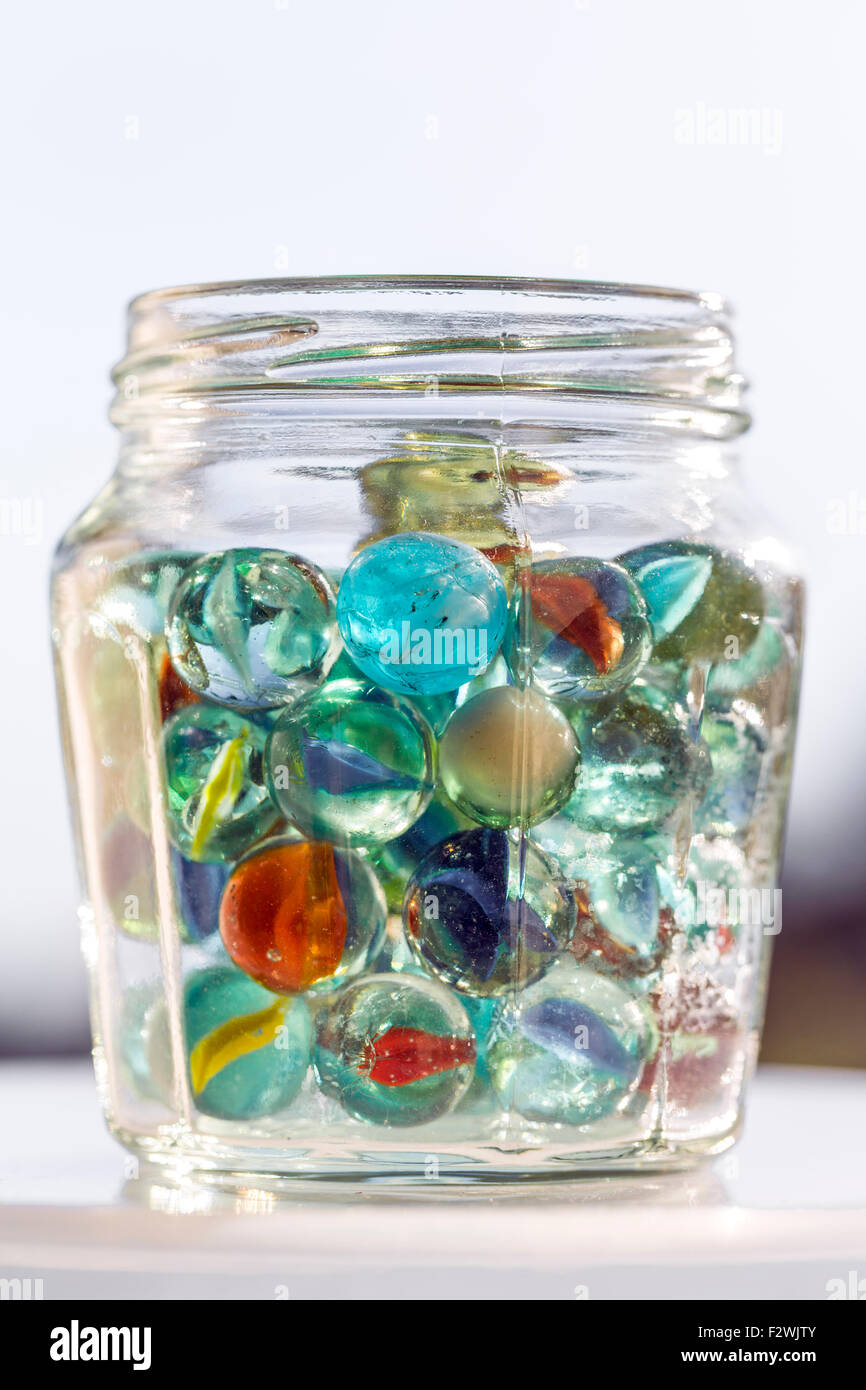 A glass jar containing marbles - Stock Image
