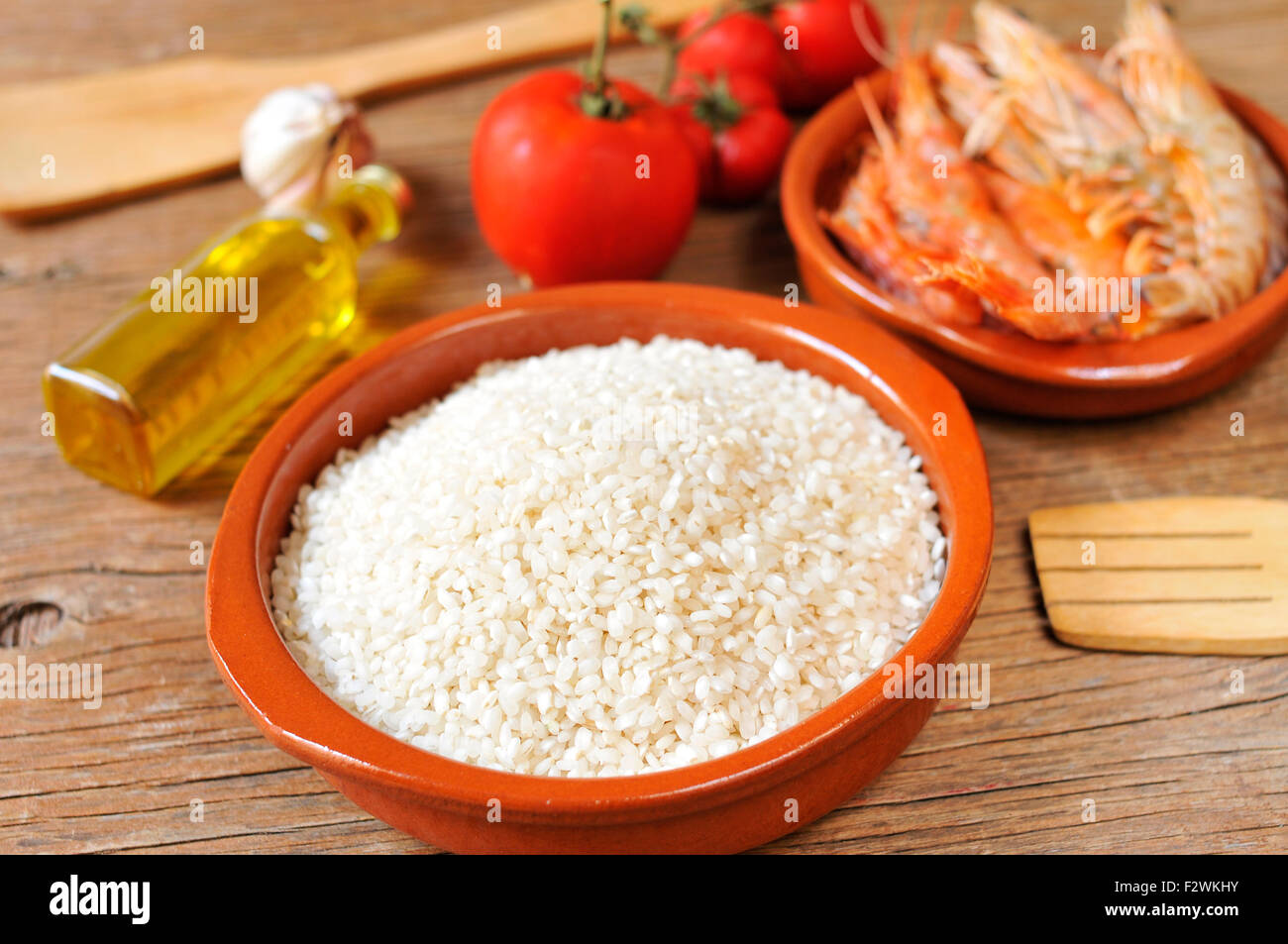 some ingredients to prepare a spanish paella or arroz negro, such as rice, tomato, garlic or shrimps, on a rustic Stock Photo