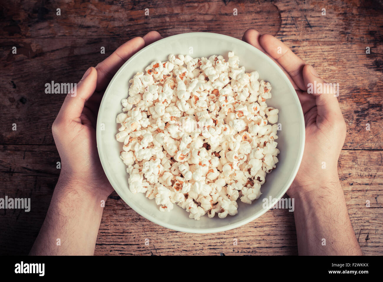 Hands holding a large bowl of popcorn on a wooden table - Stock Image