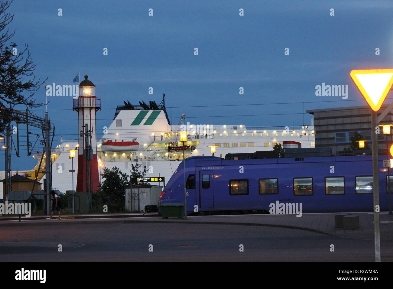 In Ystad, South Sweden, Scandinavia, Europe. Night Scene on the waterfront with a train, a cruise ship and a lighthouse. - Stock Image