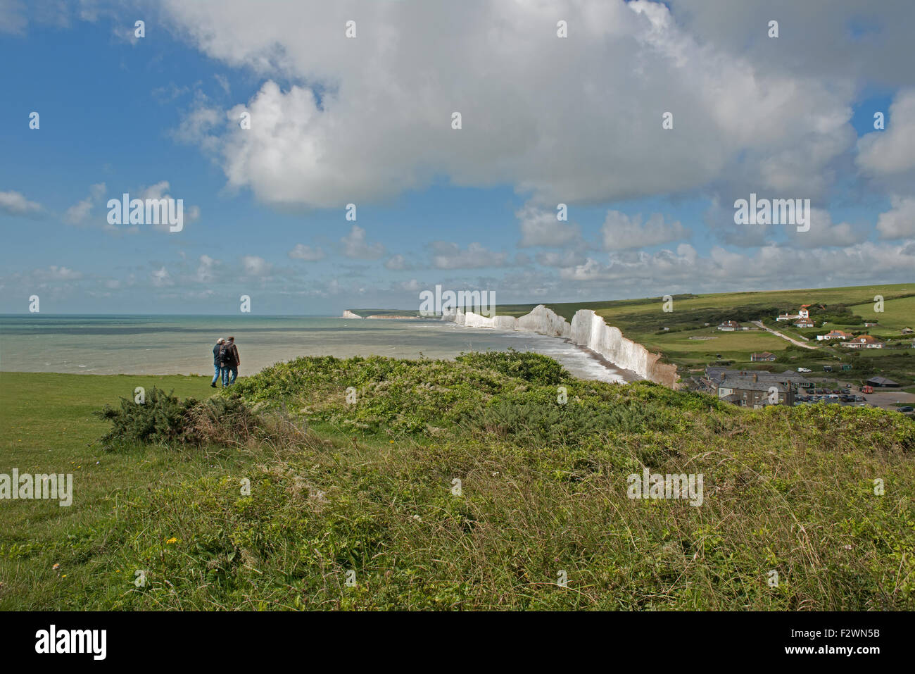 A Couple walk towards the Seven Sisters Cliffs,  from  Birling Gap, South Downs National Park, East Sussex, England, Stock Photo