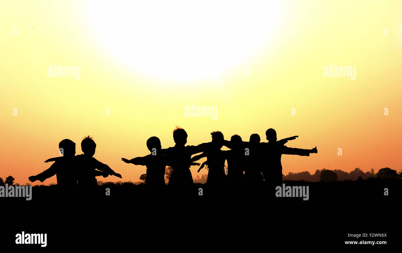 Village children returning from fields during sunset in India - Stock Image