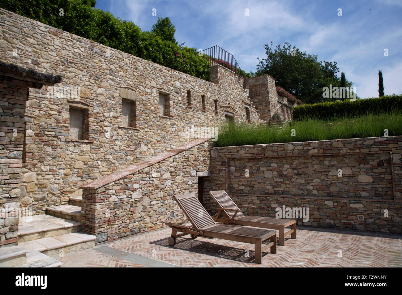 Wooden Loungers On Sunken Patio With Stone Steps And Walls In Italian Country Garden