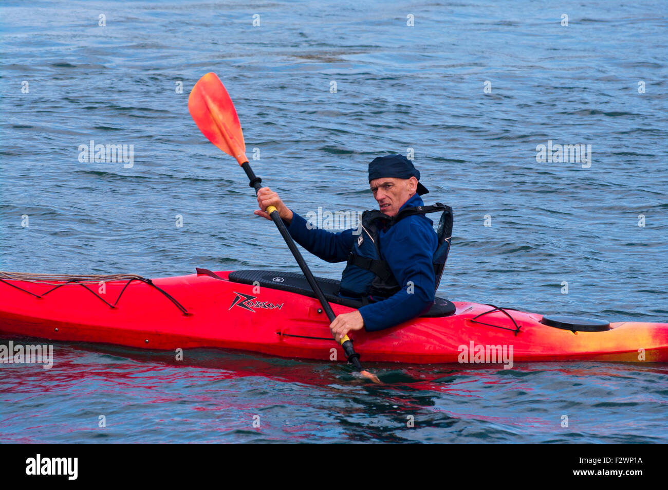 Side View Of A Person Paddling Red Robson Kayak