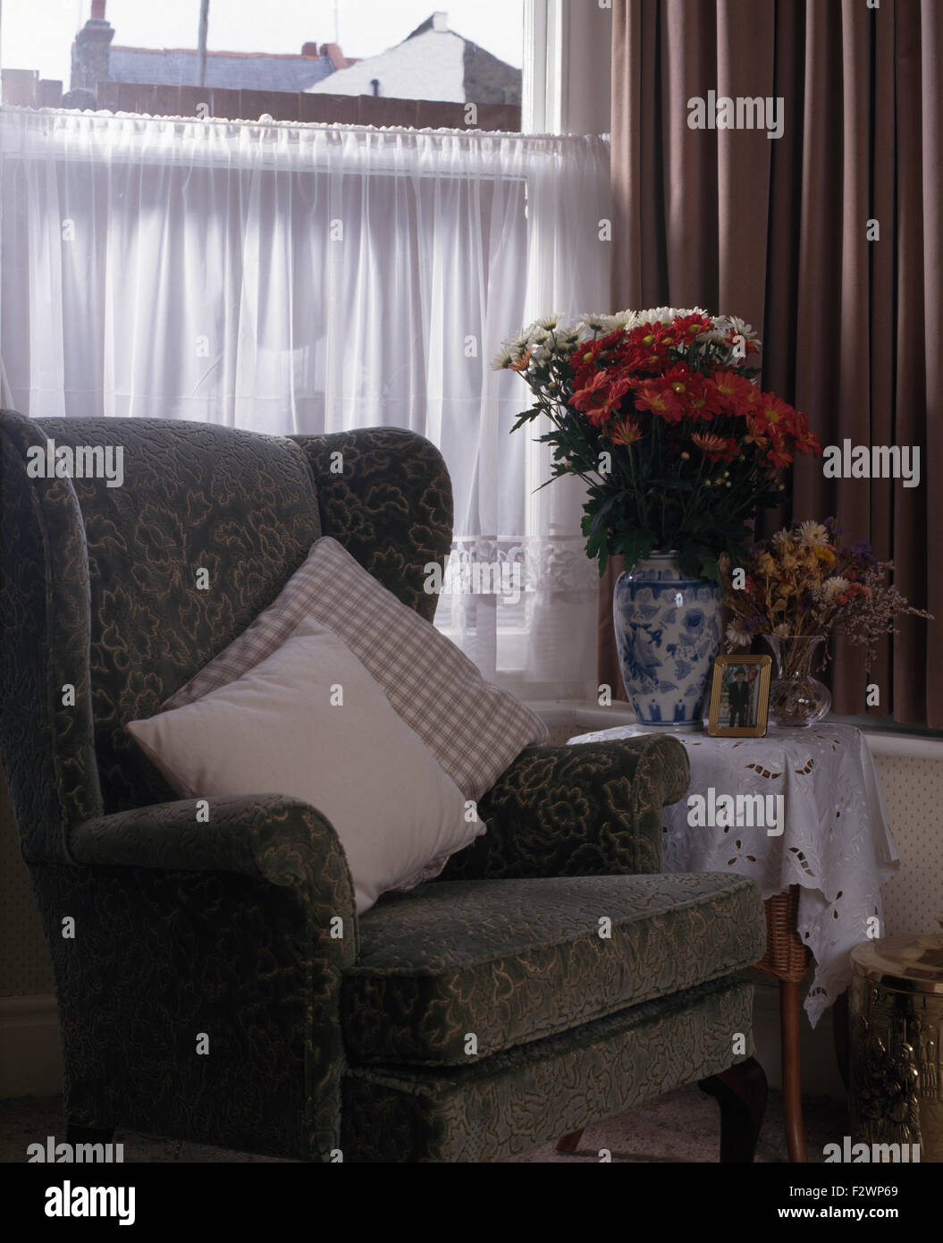 Upholstered Grey Chair In Front Of Window With A Wshite Net Cafe Curtain    Stock Image