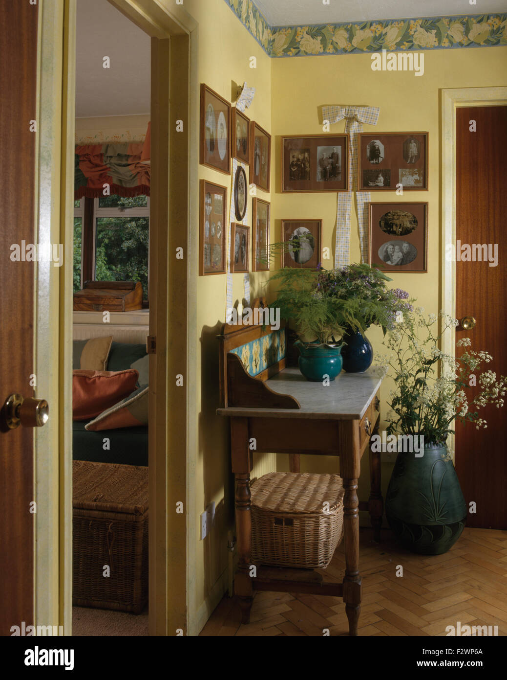 Group of framed photographs and wallpaper border in pale yellow nineties hall with an Edwardian washstand - Stock Image