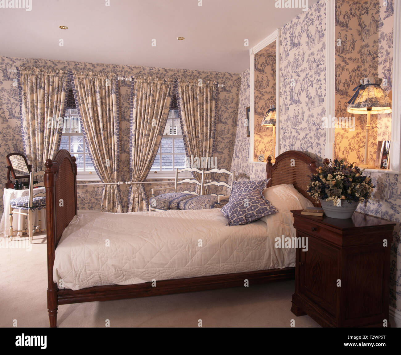 Blue Toile-de-Jouy wallpaper and matching curtains in townhouse bedroom - Stock Image
