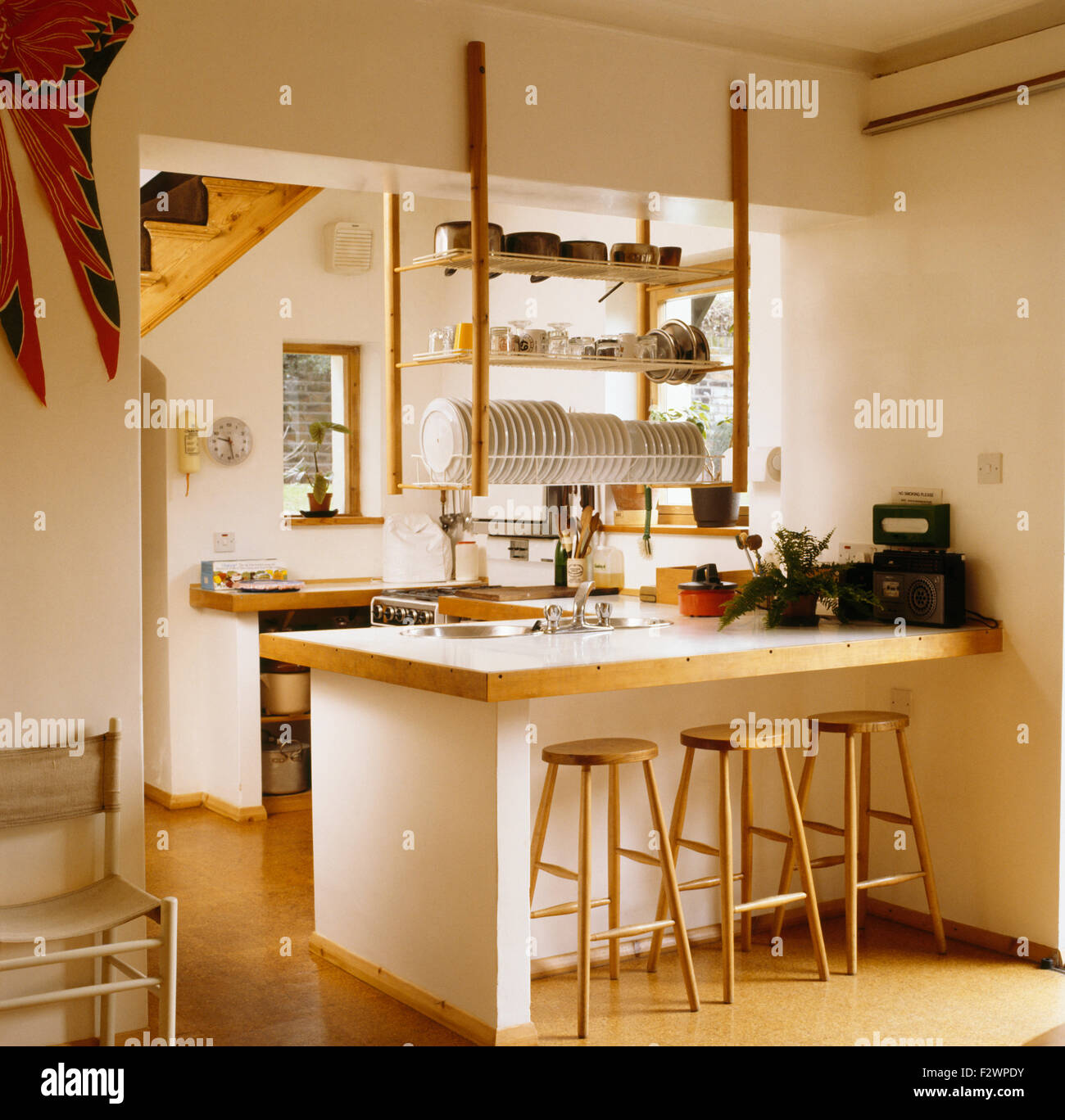Beau Wooden Stools At Breakfast Bar Below Hanging Wooden Shelves In Nineties  Kitchen