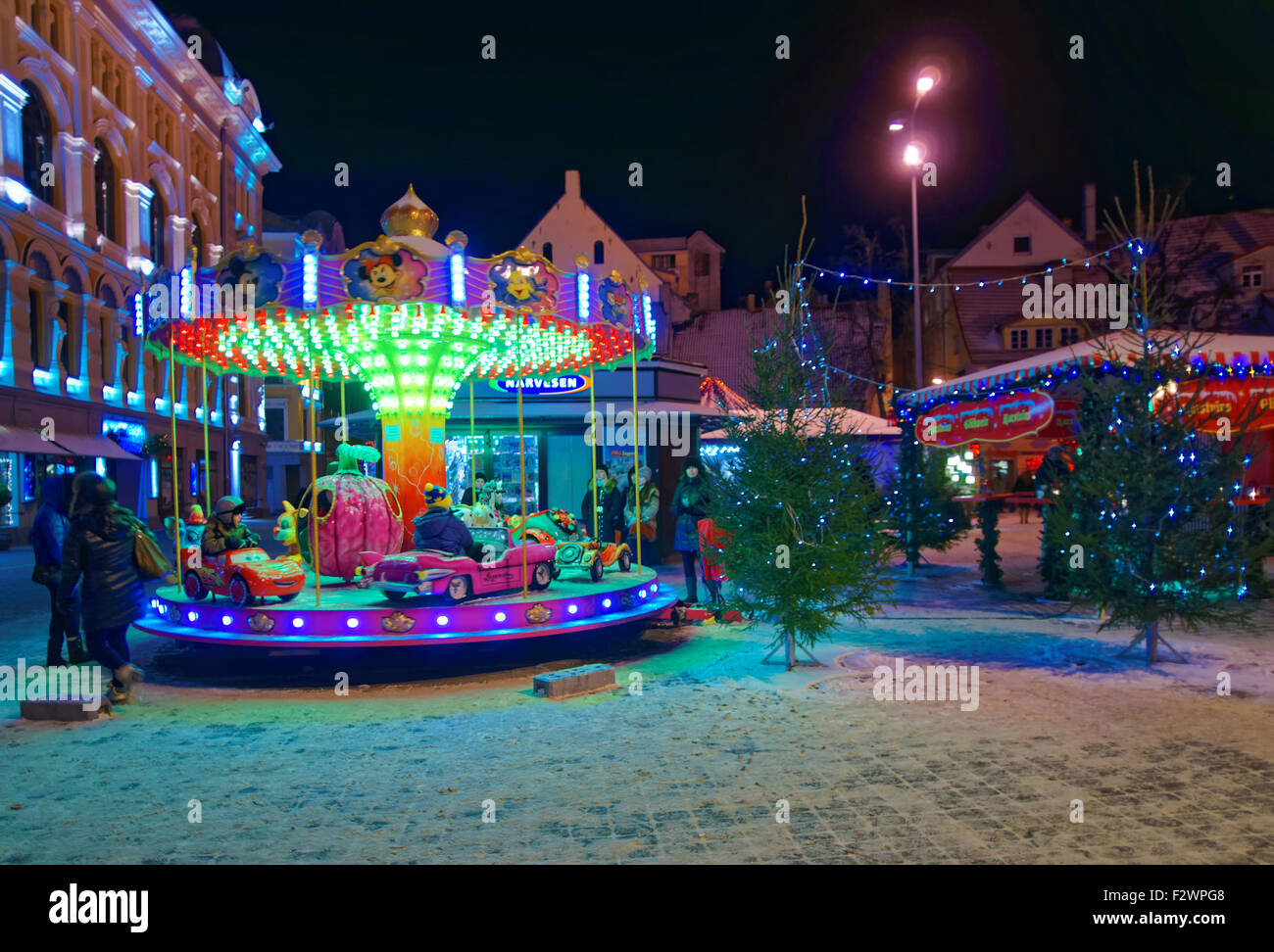 RIGA, LATVIA - DECEMBER 28, 2014: Little kids riding a merry-go-round at the traditional Christmas market in the Stock Photo