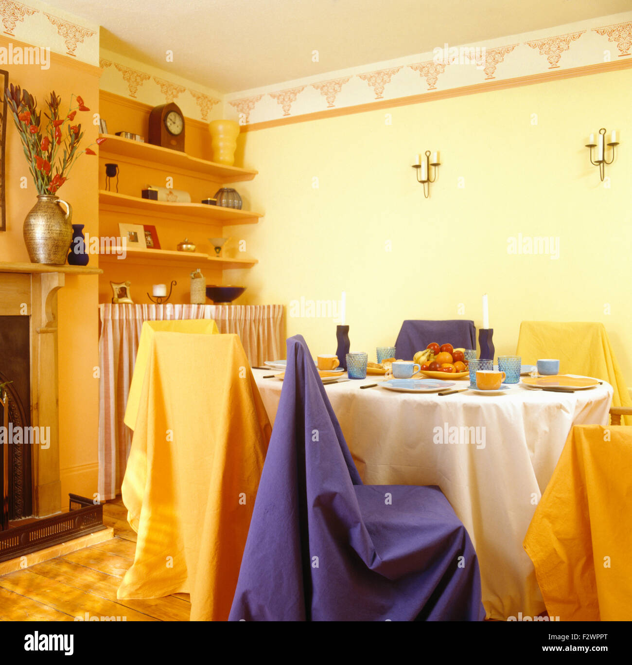 Colourful throws on dining chairs in eighties dining room before renovation - Stock Image