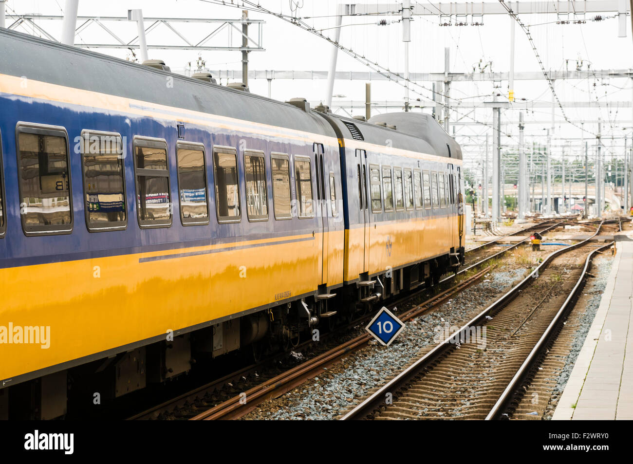 Blue and yellow train leaving Utrecht Centraal Station - Stock Image