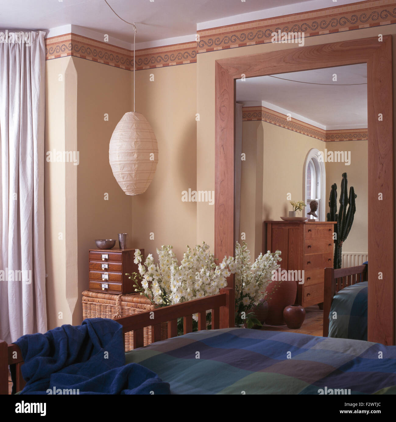 Lozenge shaped paper ceiling light in nineties bedroom with large rectangular mirror and wallpaper border - Stock Image