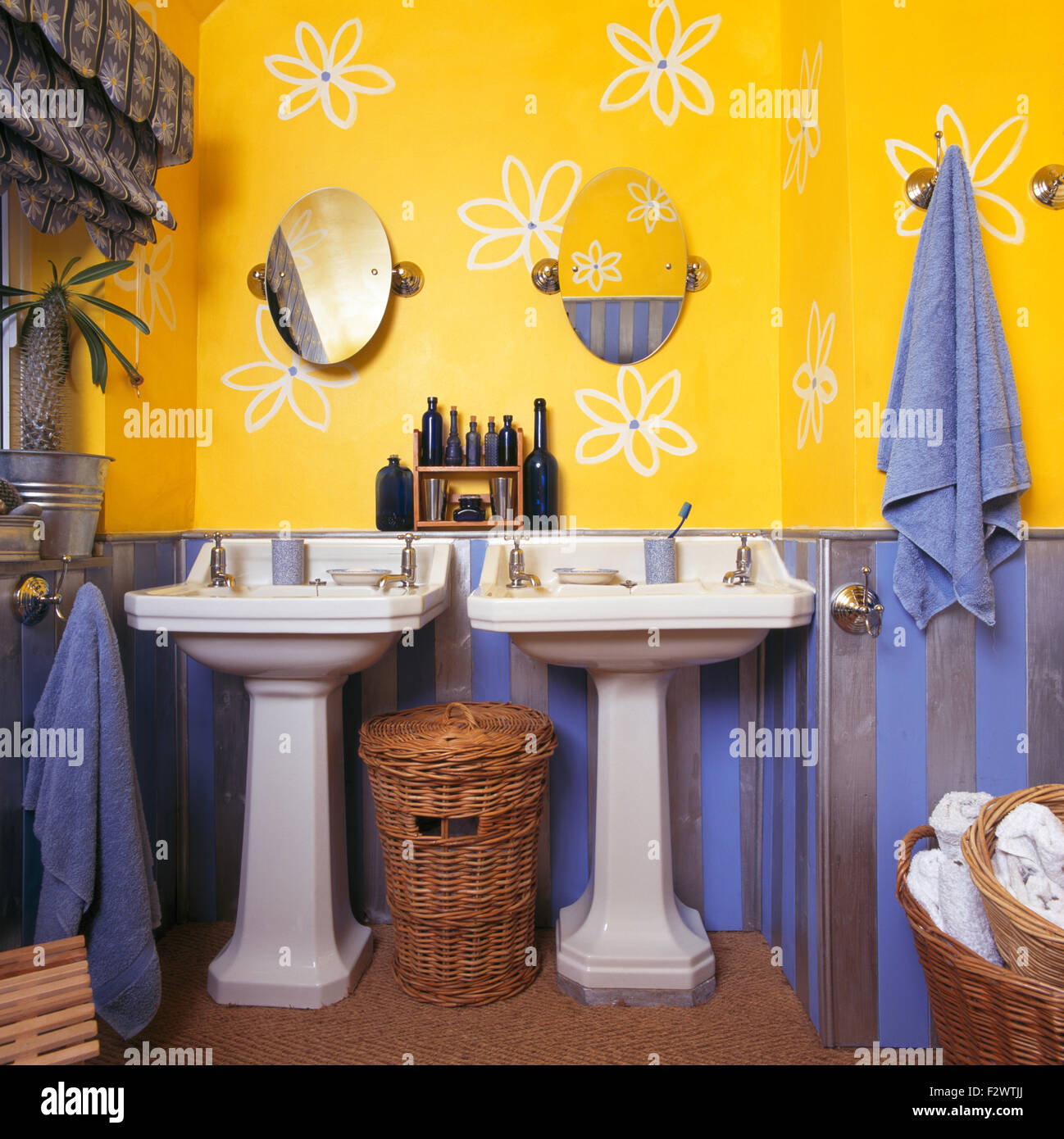 Stylised flowers drawn on wall above double pedestal basins in bright yellow and blue nineties bathroom - Stock Image