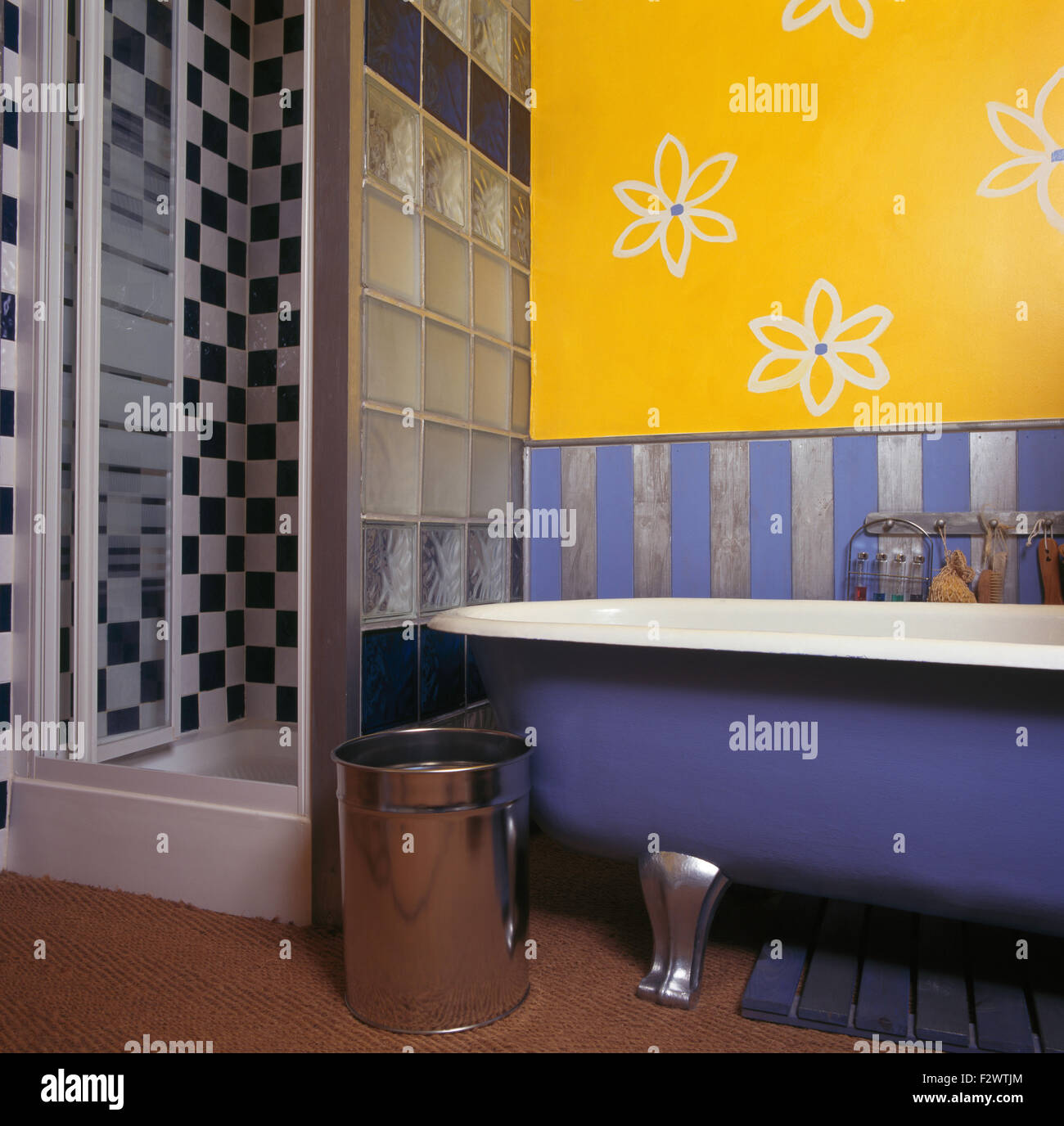 Stylised flowers drawn on wall above roll top bath in bright yellow nineties bathroom with glass shower cabinet - Stock Image