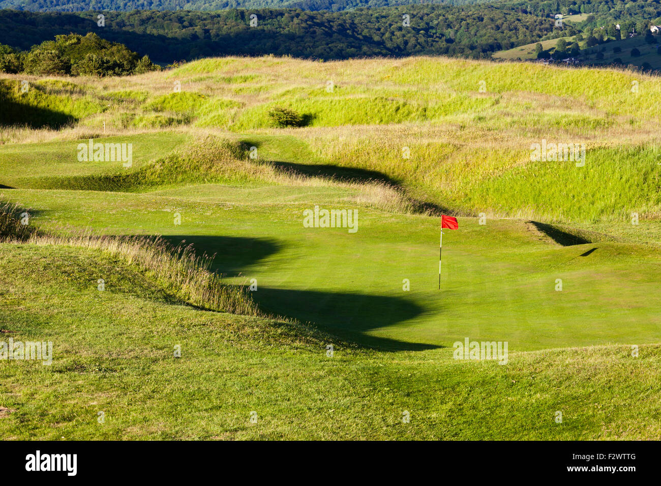 One of the greens on the golf course set among the defensive ramparts and ditches of the Iron Age hillfort on Painswick - Stock Image