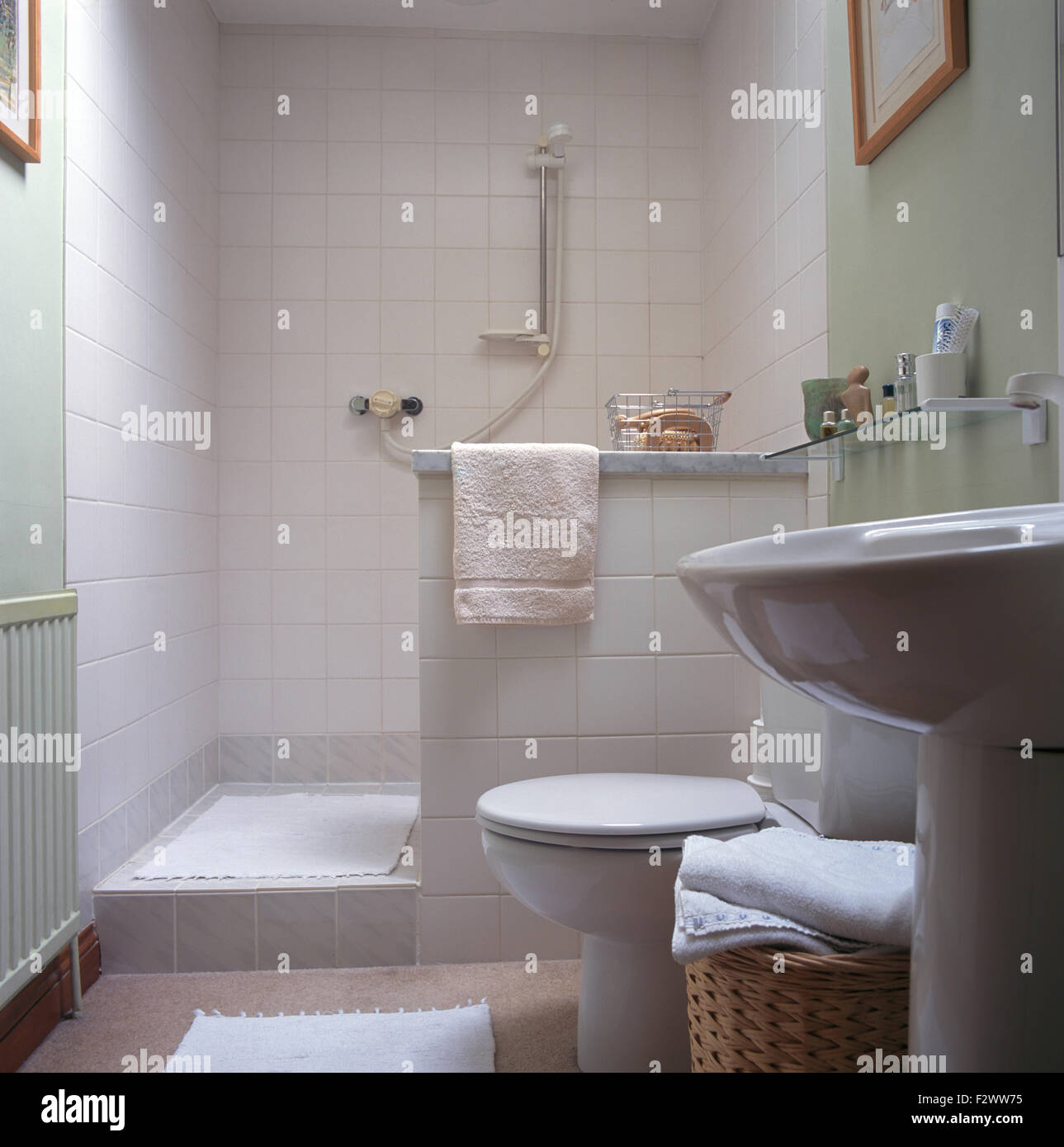 Walk In White Tiled Shower In Pale Green Bathroom With Pedestal Basin
