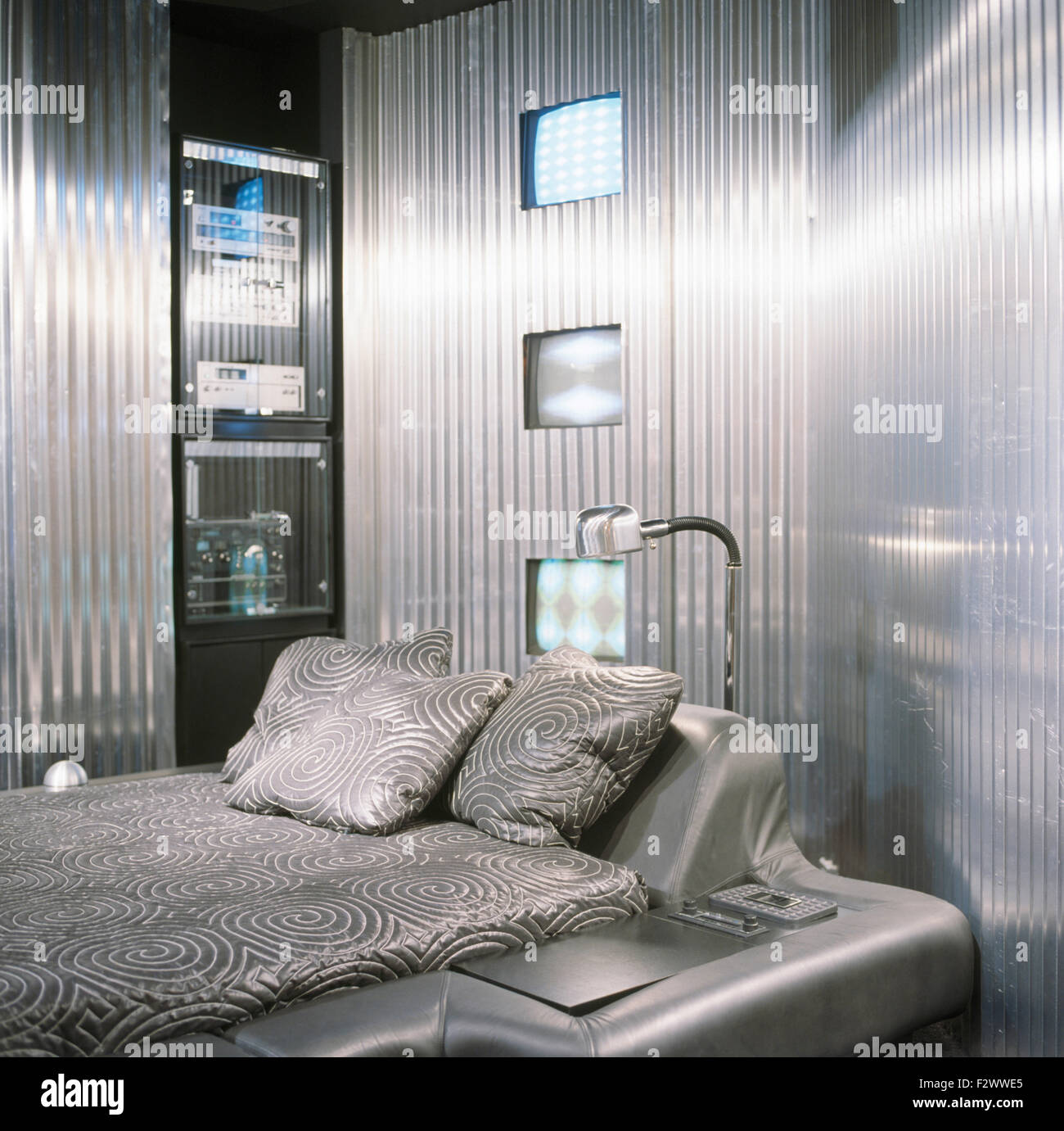 Corrugated metal walls in a silver eighties bedroom with a silver leather fitted bed - Stock Image