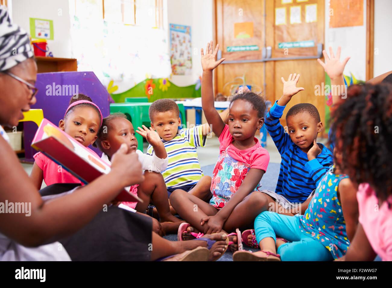 Class of preschool children raising hands to answer teacher - Stock Image