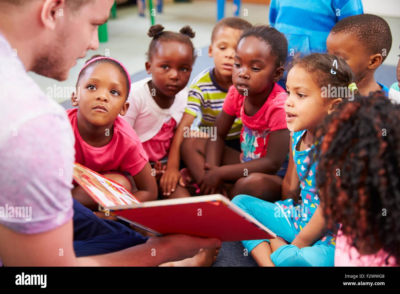 Volunteer teacher reading to a class of preschool kids - Stock Image