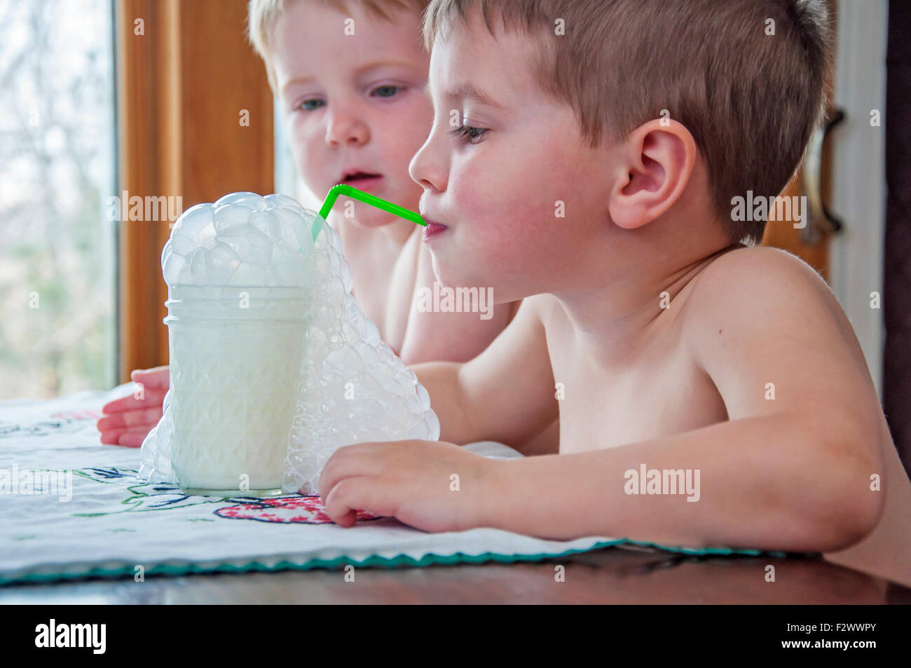 Boy blowing milk bubbles in a glass through straw - Stock Image