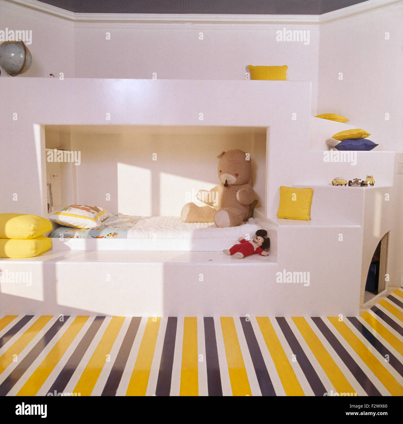 Yellow striped painted floor in child's eighties architectural style bedroom - Stock Image